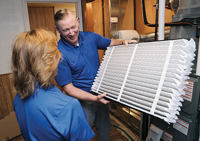 A technician showing a client a air quality filter.
